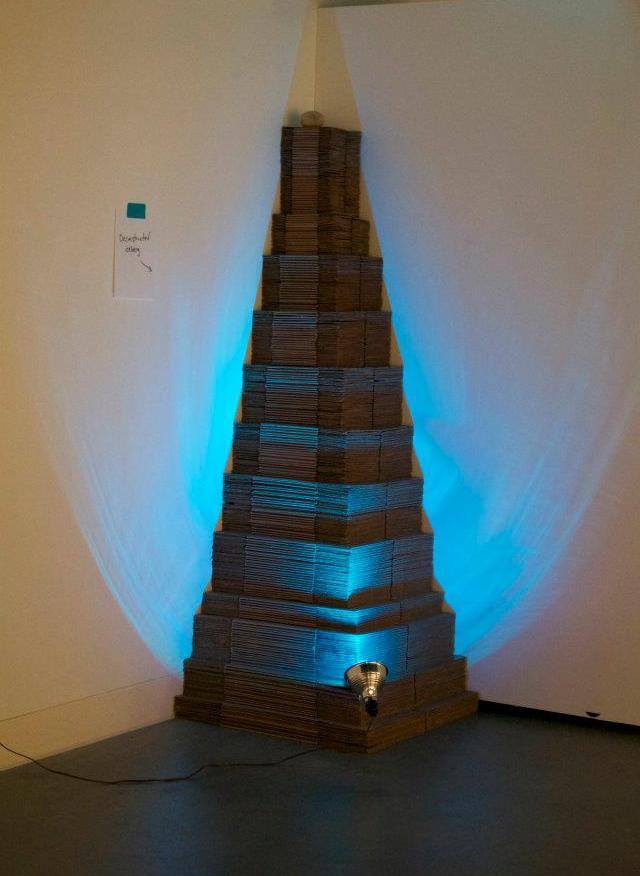 Deconstructed Iceberg, mixed media installation (cardboard, blue light, rock, tape, and hand-written sign), 2012
