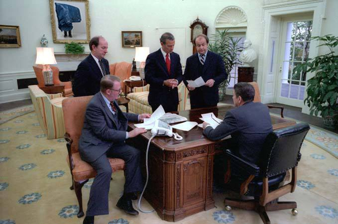 President Reagan holds an oval office staff meeting on his first full day in office (from left to right) Deputy Chief of Staff Michael Deaver, Counselor to the President Ed Meese, Chief of Staff James Baker III, Press Secretary James Brady, President Reagan. 1/21/81. Digital Intervention 2013